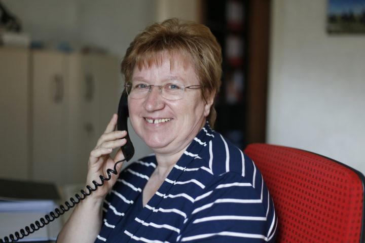 Eine Frau hält einen Telefonhörer an ihr Ohr und lächelt.
