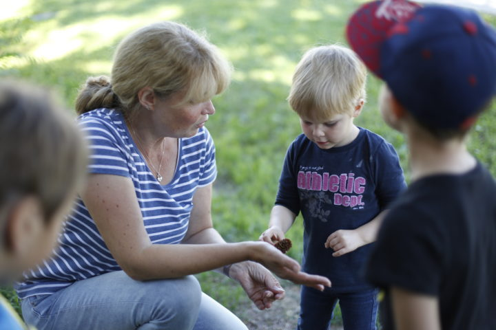 Eine Frau zeigt einem Kind auf Augenhöhe etwas in ihrer Hand.